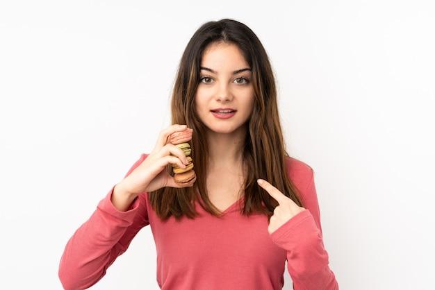 Молодая кавказская женщина на розовой стене держа красочные macarons с выражением удивления