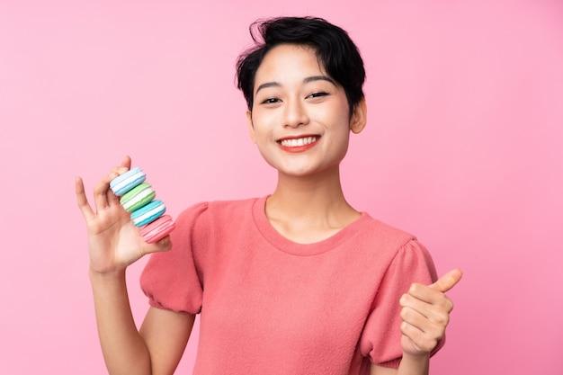 Молодая азиатская женщина держа красочные французские macarons с большими пальцами руки вверх