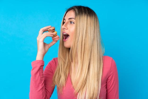 Молодая женщина над изолированной синей стеной держит красочные французские macarons и ест его