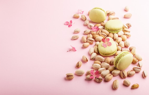 Зеленые macarons или миндальное печенье торты с фисташками на пастельных розовом фоне. вид сбоку, копия пространства.