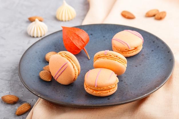 Оранжевый macarons или миндальное печенье торты на синей керамической пластины на серой бетонной поверхности. вид сбоку, выборочный фокус.