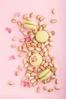 Зеленые торты macarons или миндальное печенье с фисташками на пастельных розовом фоне. вид сверху, крупный план.