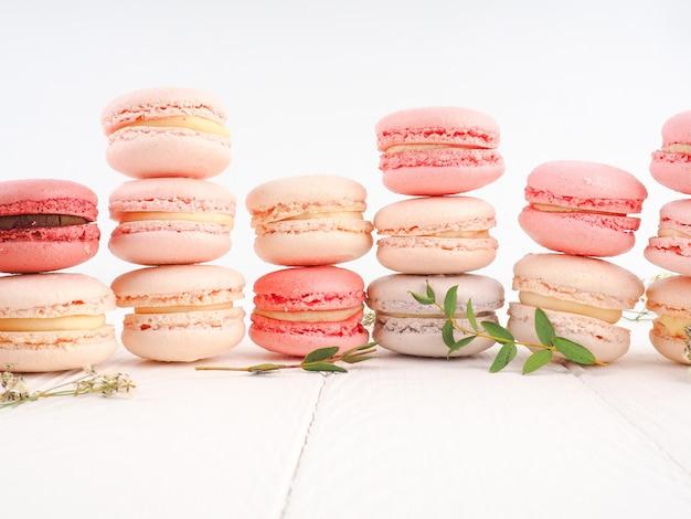 Красочный французский или итальянский macarons стека на белый деревянный стол. десерт подается с послеобеденным чаем или кофе-брейком