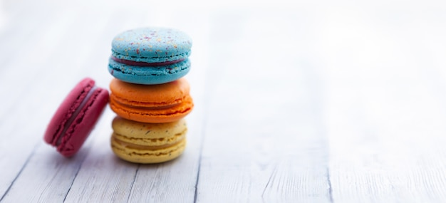 Французские миндальные печенья. стог красочного macaroon на деревянном столе, copyspace