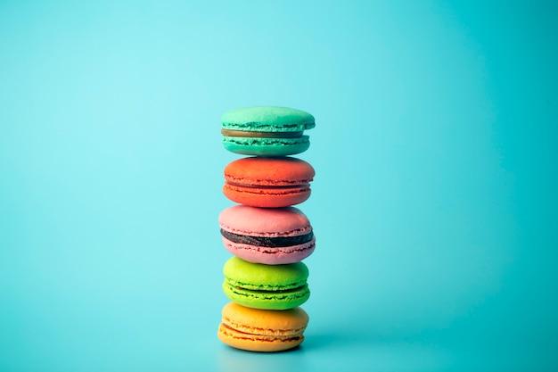 Покрашенные печенья macaroon (macarons) на голубой предпосылке. яркая праздничная выпечка, десерты и сладости. выпечка фон