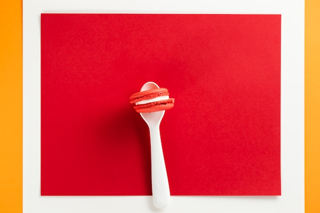 Macaroon in a spoon with red background