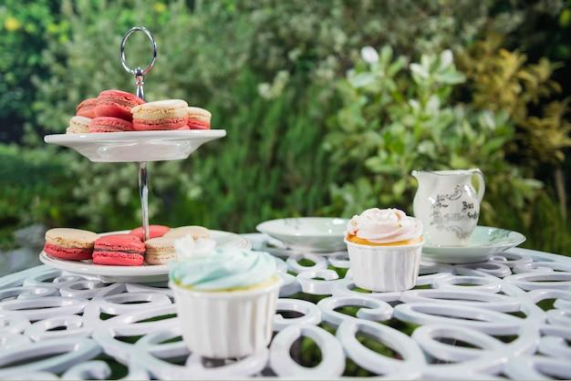 Много macaroon с розовым, белым цветом и торт чашки на плите установили в сад. сладкий десерт расслабиться концепция