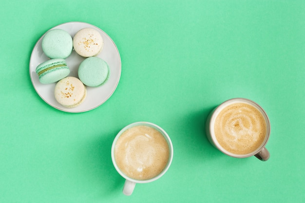 Macaroons капучино 2 чашек кофе и сладостного десерта в белой плите на бумаге мяты. утренний кофе кубок концепции. вид сверху. квартира лежала.