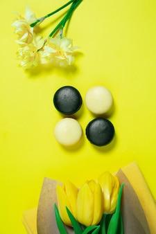 マカロンと花。黄色の表面にモノクロのスタイリッシュでトレンディな構成。上面図、フラットレイ。周りのいつものものの純粋な美しさ。広告のコピースペース。休日、食べ物、ファッション。