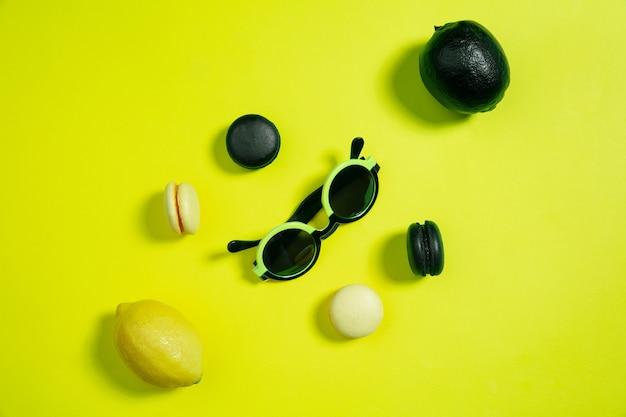 マカロンとレモン。背景に黄色のモノクロスタイリッシュでトレンディな構成。上面図、フラットレイ。周りのいつものものの純粋な美しさ。広告のコピースペース。休日、食べ物、ファッション。