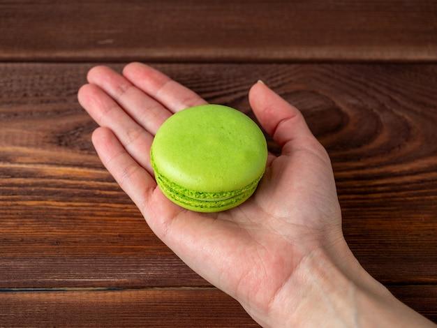 マカロンは、茶色の木製の背景の上に広げられた手のひらの上に緑色です。フランス産の美味しいスイーツ