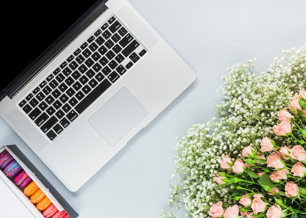 Macaroons in box; laptop and bunch of flowers on white background