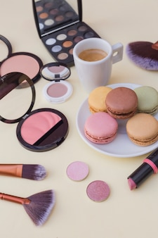 Macaroons breakfast with coffee and cosmetics product on beige background