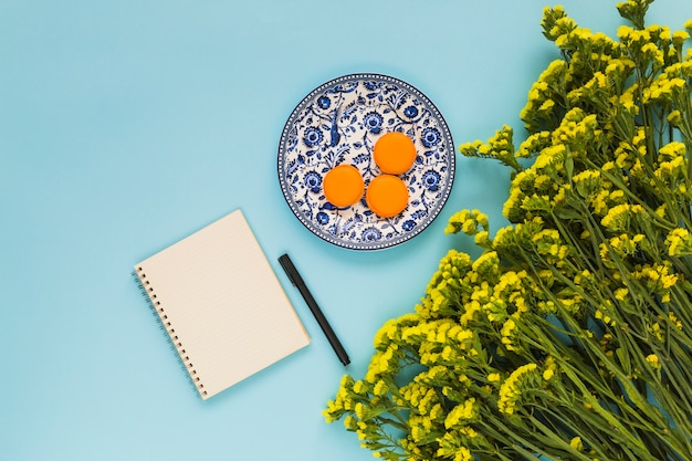 Macaroons on ceramic plate; spiral notepad; pen and bunch of yellow flowers on blue background
