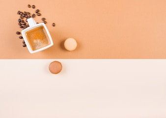Macaroons; coffee cup; and roasted coffee beans on dual background
