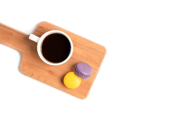 Macaroons and a cup of coffee on wooden board