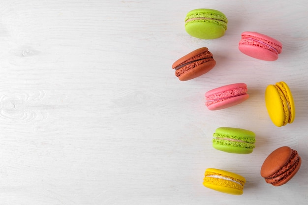 마카롱. 하얀 나무 탁자에 있는 맛있는 색깔의 프랑스 마카로니 케이크. 텍스트에 대 한 장소입니다. 평면도