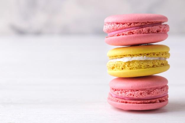 Миндальное печенье. вкусные цветные французские макароны на белом деревянном столе. место для текста