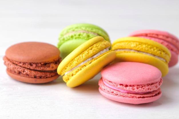 Миндальное печенье. вкусные цветные французские макароны на белом деревянном столе.