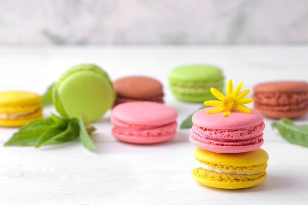 Миндальное печенье. вкусные цветные французские пирожные с макарунами с желтым цветком на белом деревянном столе