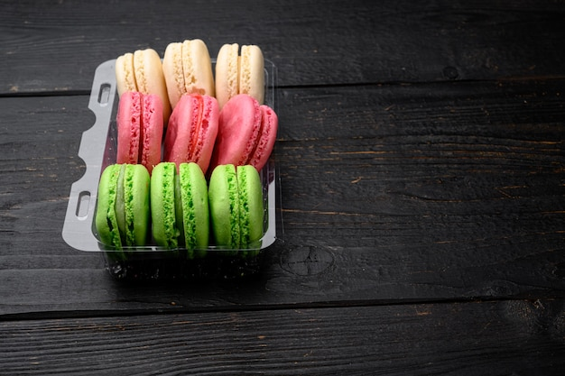 Macaroons. delicious french desserts set, in plastic pack, on black wooden table background, with copy space for text