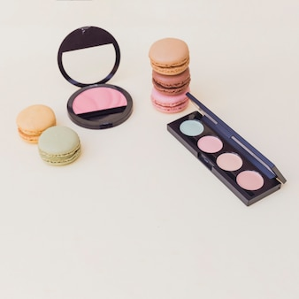 Macaroons; eye shadow palette and pink blusher on colored background