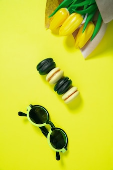 Macaroons and flowers. monochrome stylish and trendy composition in yellow color on surface. top view, flat lay. pure beauty of usual things around. copyspace for ad. holiday, food, fashion.