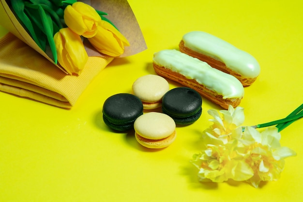 Macaroons and flowers. monochrome stylish and trendy composition in yellow color surface. top view, flat lay. pure beauty of usual things around. copyspace for ad. holiday, food, fashion.
