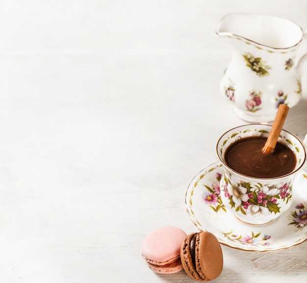 Macaroons and hot chocolate with cinnamon stick in ceramic cup on white textured backdrop