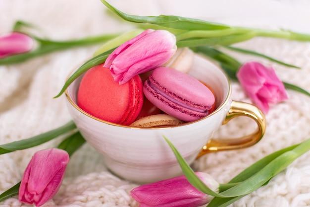 金色のマグカップとピンクのチューリップのマカロン