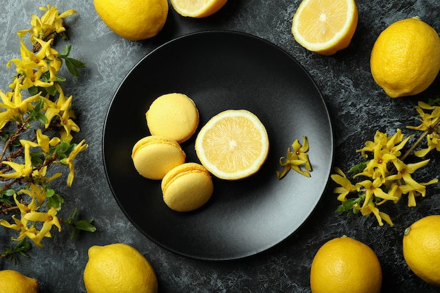 Миндальное печенье, лимоны и цветы на черном дымчатом фоне