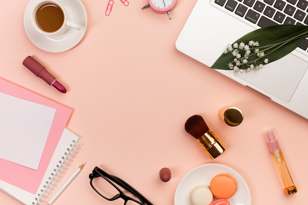 Macaroons,makeup products,spiral notepads,coffee cup and laptop on peach colored backdrop