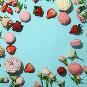 Macaroons, marshmallows, flowers and strawberry on blue background