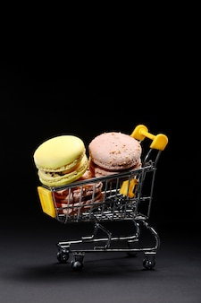Macaroons in metal shopping basket. studio photo. macaroons on dark wall, colorful french cookies macaroons. macaroons. confectionery photography concept in black wall portrait.