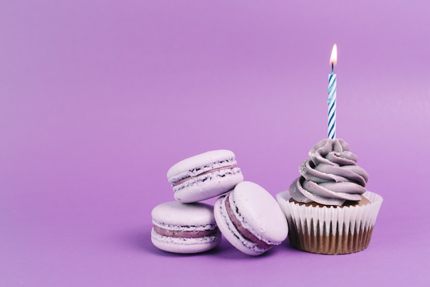 Macaroons near cupcake with candle Free Photo