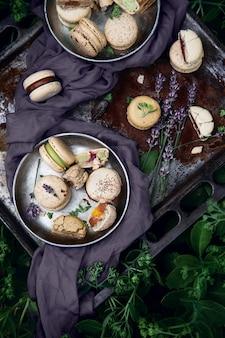 Миндальное печенье на старом противне и цветы лаванды как украшение среди зеленых кустов. вид сверху.