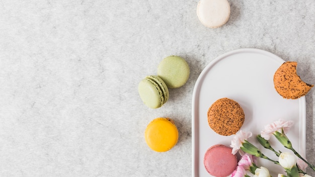 Macaroons on plate over textured background