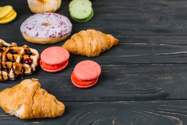 Macaroons; waffles; croissant and donuts on wooden table
