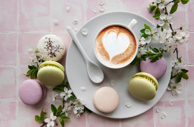 Миндальное печенье с чашкой кофе и веткой белых цветов на поверхности розовой плитки