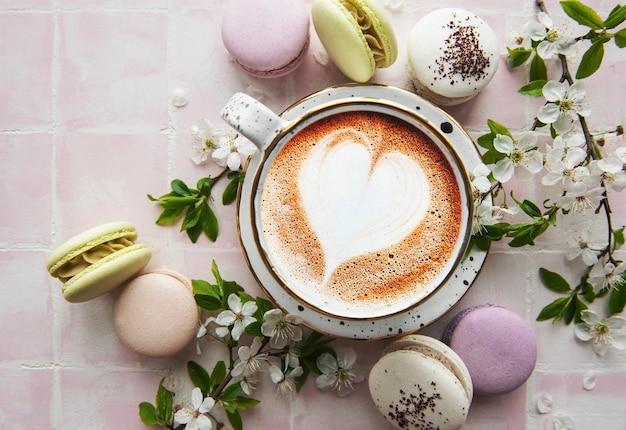 커피 한 잔과 흰 꽃 가지가 있는 마카롱