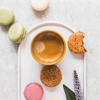 Macaroons with coffee cup on plate over the marble backdrop