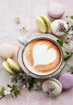 Macaroons with a cup of coffee and a branch of white flowers on a pink tile surface