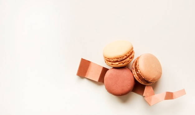 Macaroons with folded paper against white background