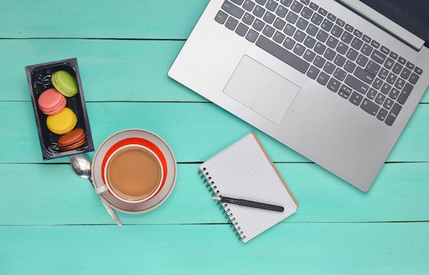 Компьтер-книжка, покрашенные печенья macaroons, чашка кофе, тетрадь с ручкой на голубой деревянной таблице. вид сверху. плоская планировка