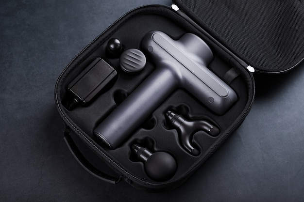 Machine for body massage in a case on a black background.
