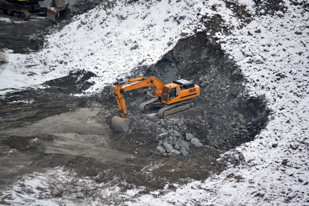 Machine for breaking stones in granite quarry in winter snowy day