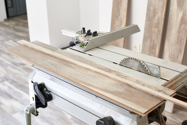 Machine of circular saw to cut wood. the process of installing laminate wooden on the floor. home construction.
