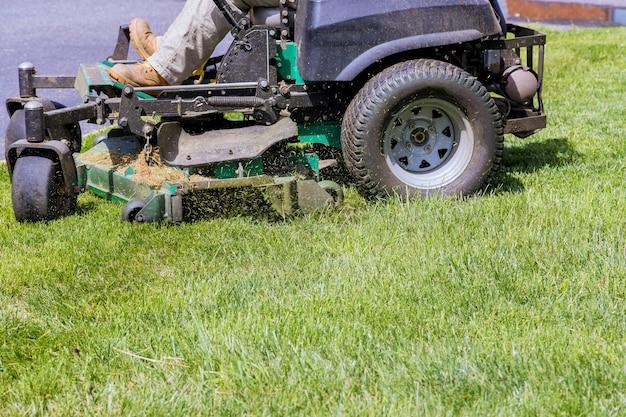 庭の緑の草の芝刈り機で芝生を切るための機械。