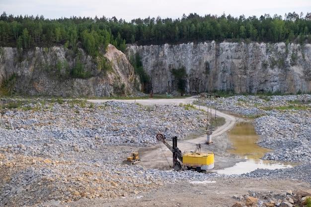 深い花崗岩の採石場の底で花崗岩を採掘するための機械
