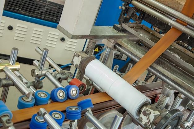 The machine glues the pvc tape onto the aluminum profile. workshop for the production of pvc profile